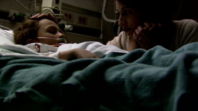 woman caressing child in hospital bed - brechreiz stock-videos und b-roll-filmmaterial