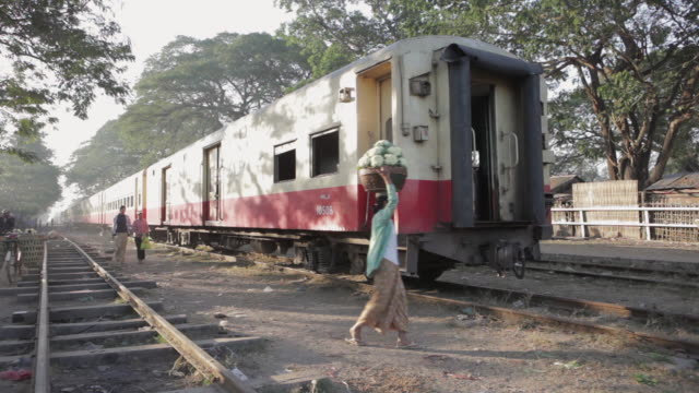 ws a woman carries a basket of cabbages past a stationary train / pyay, myanmar - ミャンマー点の映像素材/bロール