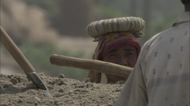a woman carries a large basket of sand on her head. available in hd. - balance stock videos & royalty-free footage