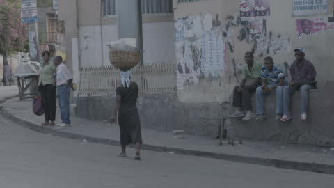 woman carries basket on head on port-au-prince street - ハイチ点の映像素材/bロール