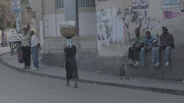 woman carries basket on head on port-au-prince street - haiti stock videos & royalty-free footage