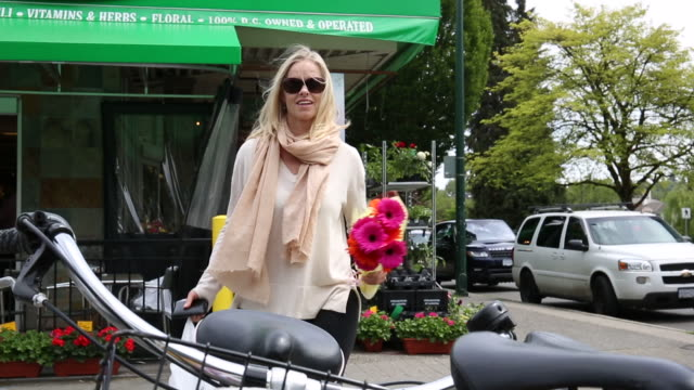 woman carries groceries and flowers to parked bicycle - garden center stock videos and b-roll footage