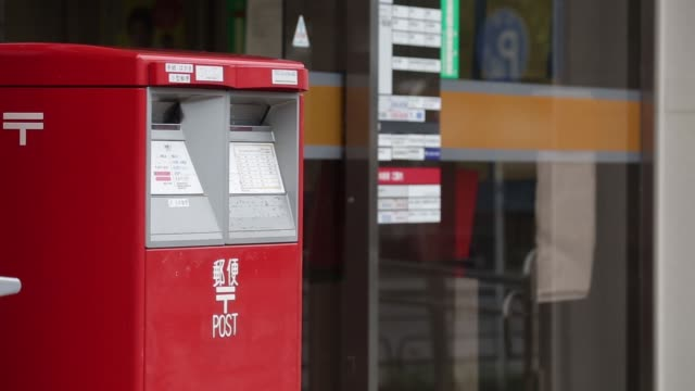 woman carries parcels into a japan post co. branch in tokyo, japan, on tuesday, sept. 8 a japan post co. mail box stands in tokyo, pedestrians and... - mail点の映像素材/bロール