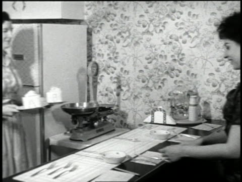 """b/w 1959 woman carrying 2 plates with food (1 marked """"a"""", 1 marked """"b"""") to counter for taste test - 1959 stock videos & royalty-free footage"""