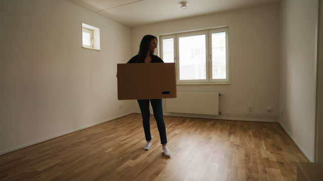 woman carrying a box into her new apartment - moving house stock videos & royalty-free footage
