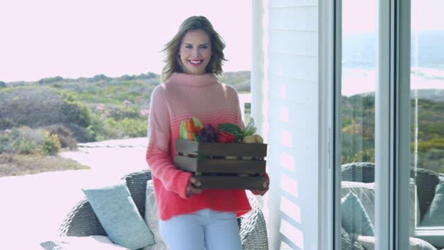 vidéos et rushes de a woman carrying a box of vegetables - seulement des jeunes femmes