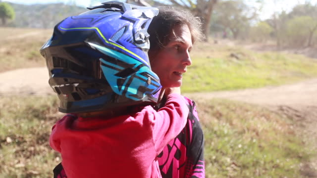 a woman carrying a young boy with a helmet on walking towards a pickup truck on a sunny summer day - kelly mason videos stock videos & royalty-free footage