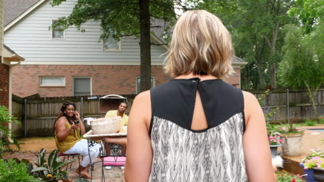 MS TS Woman carrying appetizer out to table while hanging out with friends during backyard party