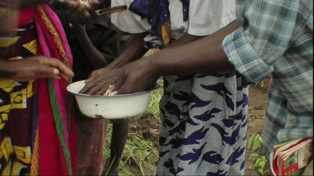 ms zo zi woman carrying baby and sharing beans / mpika, zambia - legume family stock videos and b-roll footage