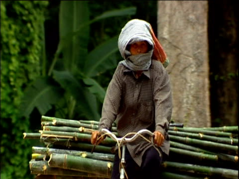 woman carrying bamboo on bike wearing turban cambodia - cambodia stock videos and b-roll footage