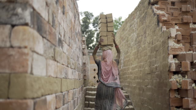 Woman carrying bricks on her head