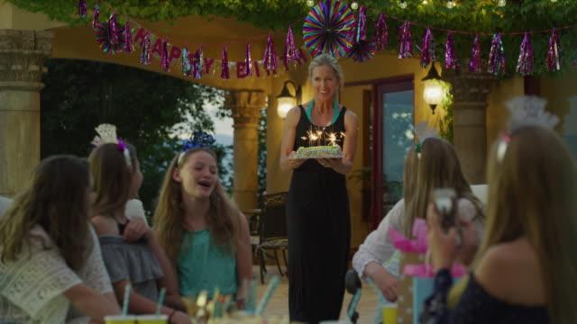 vídeos y material grabado en eventos de stock de woman carrying cake with sparklers to girls at birthday party / cedar hills, utah, united states - encuadre de tres cuartos