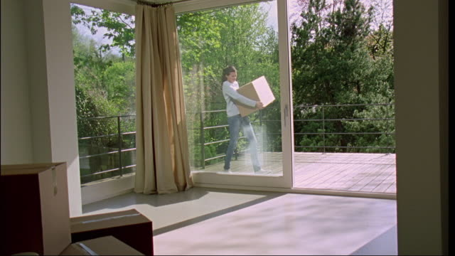 ms, pan, woman carrying cardboard box from balcony into apartment, brussels, belgium - haarzopf stock-videos und b-roll-filmmaterial