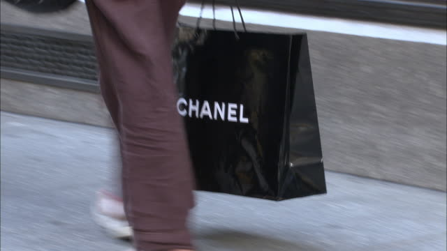 cu, pan, woman carrying chanel shopping bag walking on street, low section, fifth avenue, new york city, new york, usa - ブランド名点の映像素材/bロール