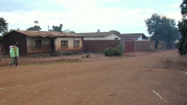 vídeos de stock e filmes b-roll de ws, woman carrying child on back walking on dirt road, lilongwe, malawi - malávi