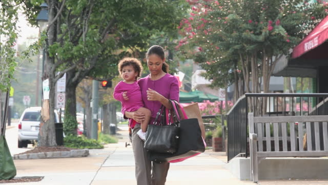 MS PAN Woman carrying daughter (18-23 Months), walking on city street / Richmond, Virginia, USA