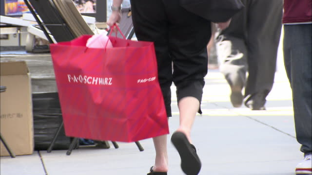 cu, woman carrying fao schwarz shopping bag, low section, fifth avenue, new york city, new york, usa - carrying stock-videos und b-roll-filmmaterial