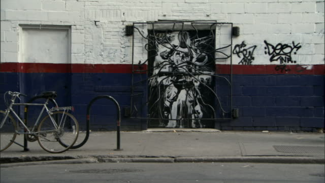 ws woman carrying fuel can past graffiti-covered wall / manhattan, new york, usa - carrying stock videos & royalty-free footage