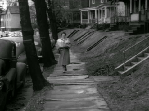 b/w 1950 woman carrying groceries + packages walking on suburban sidewalk / connecticut - shopping bag stock videos & royalty-free footage