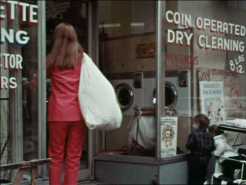 1969 rear view woman carrying laundry bag entering laundromat / greenwich village, nyc - waschsalon stock-videos und b-roll-filmmaterial