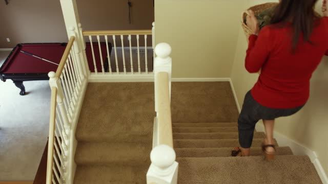 stockvideo's en b-roll-footage met ws woman carrying laundry basket downstairs / renton, washington, usa  - wasmand