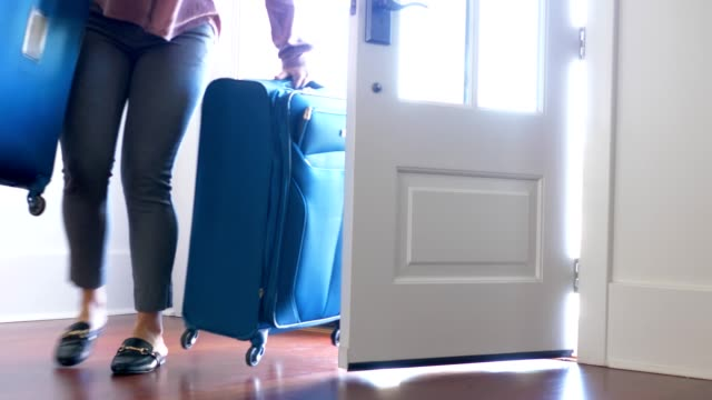 Woman carrying luggage into home ar front door.