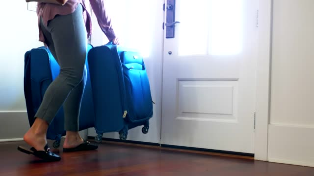 woman carrying luggage out front door at home. - bagaglio video stock e b–roll