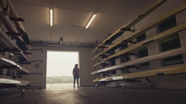 vídeos de stock, filmes e b-roll de mulher carregando barco a remo da casa de barcos - esporte aquático