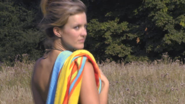 woman carrying towel through field, uk - sideways glance stock videos & royalty-free footage