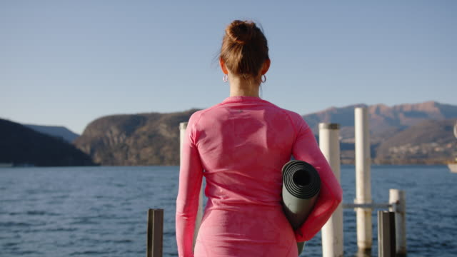 woman carrying yoga mat walking out on dock - 40 44 years stock videos & royalty-free footage