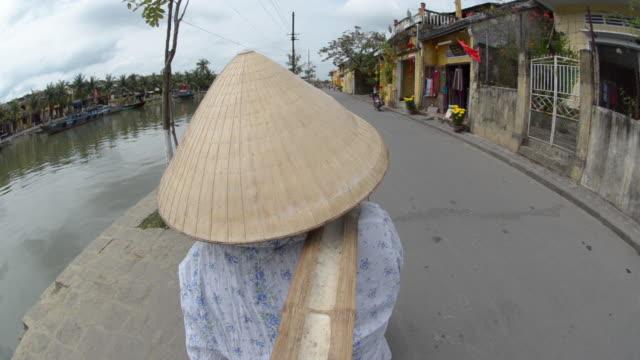 Woman carrying yoke baskets of fruit in street, Hoi An, Vietnam