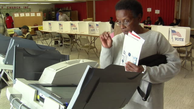 MS, Woman casting her vote at electronic voting machine, Toledo, Ohio, USA