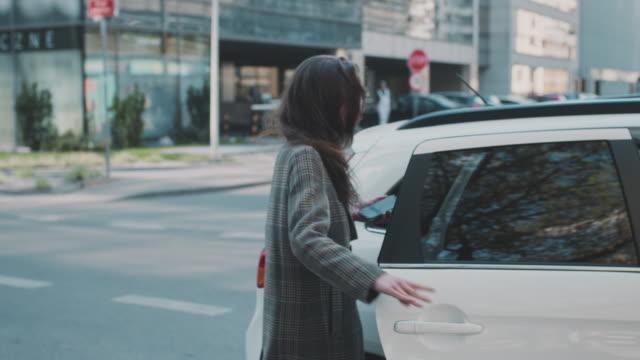 donna che cattura un uber nel centro della città. salire in macchina - taxi video stock e b–roll