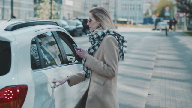 vídeos de stock e filmes b-roll de woman catching an uber in the city center. getting into car - táxi