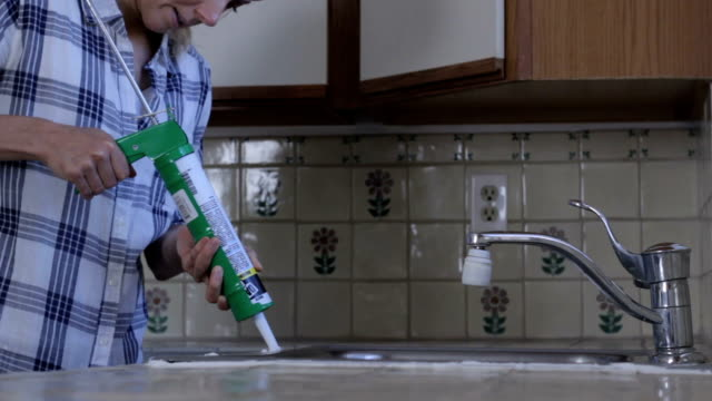 diy woman caulks kitchen sink high speed - caulk gun stock videos and b-roll footage