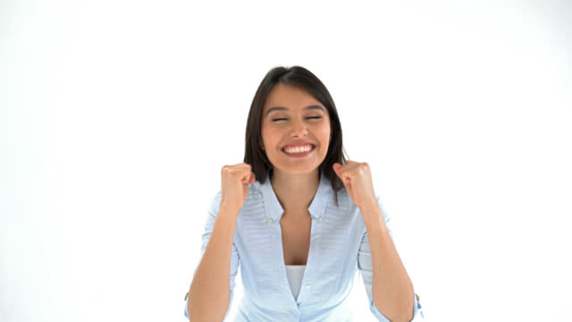 Woman celebrating cheerfully and smiling looking at the camera
