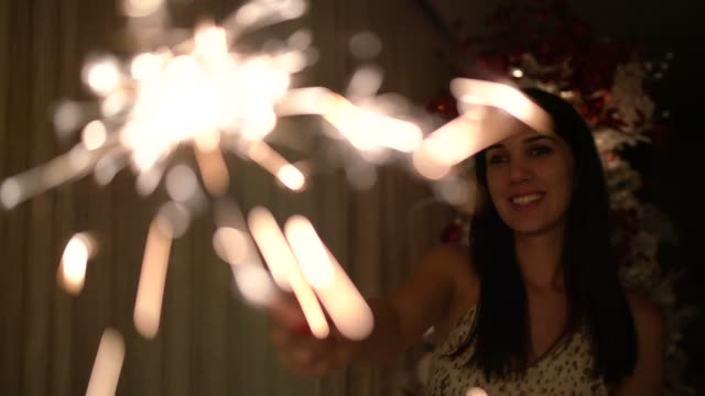 woman celebrating christmas / new year with sparkler at home - wishing well stock videos & royalty-free footage