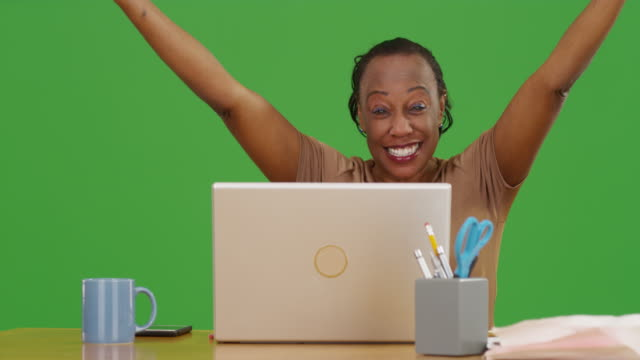 woman celebrating while using her computer on green screen - maestra video stock e b–roll