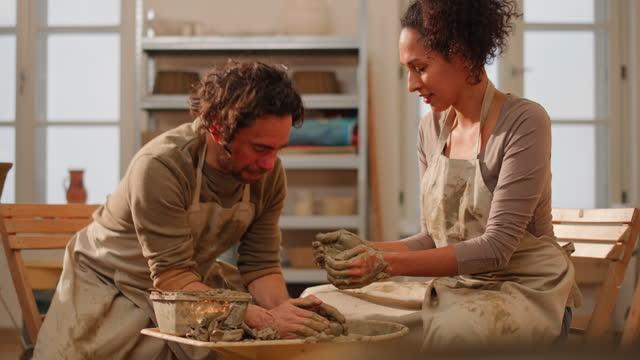 車輪の上に粘土を中心に女性と彼女の男性の先生によって助けられている - 陶芸家点の映像素材/bロール