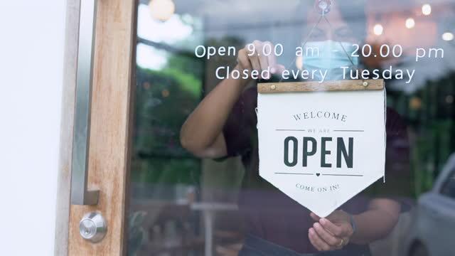 donna cambiare segno di stoffa chiuso per aprire il rallentatore - insegna di negozio video stock e b–roll