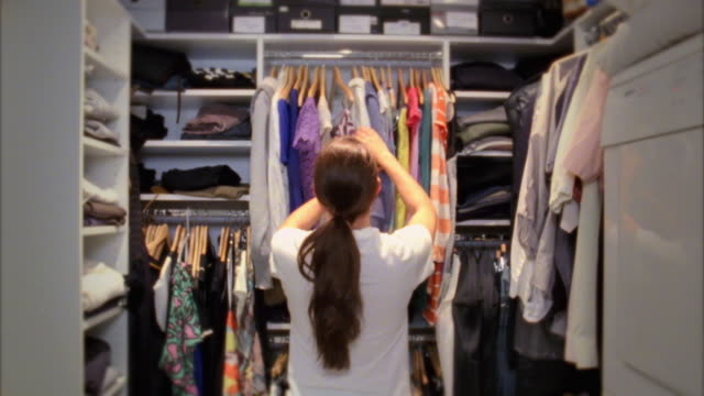 stockvideo's en b-roll-footage met ms woman changing clothes in walk-in closet, new york city, new york, usa - kleding