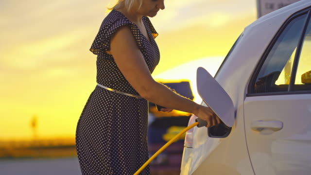 slo mo woman charging a car at the charging station at sunset - electric vehicle stock videos & royalty-free footage