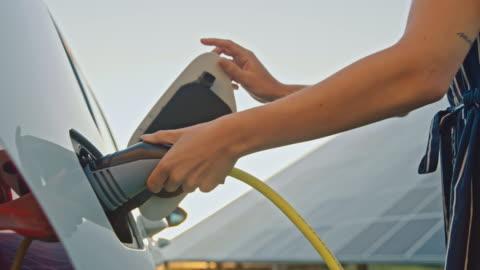 vídeos y material grabado en eventos de stock de slo mo woman cargando su coche en la estación de carga de vehículos eléctricos alimentado por energía solar - cargar