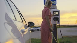 SLO MO Woman charging her electric car at the electric vehicle charging station