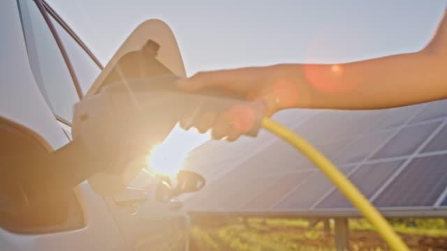 vídeos de stock, filmes e b-roll de slo mo mulher carregando seu carro elétrico por energia solar - energia solar