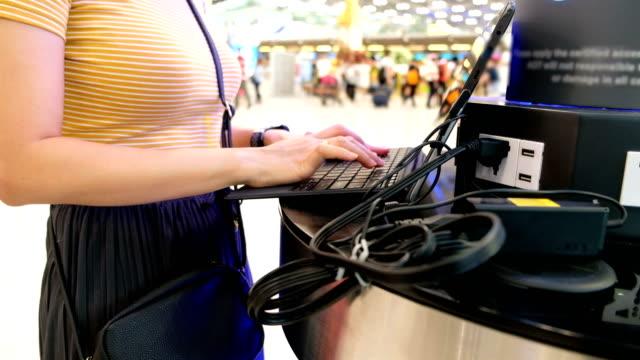 vídeos y material grabado en eventos de stock de mujer cargando su portátil en puntos de carga en la terminal del aeropuerto - enchufe