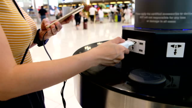 woman charging her mobilephone at charging points station in airport terminal - plug socket stock videos & royalty-free footage