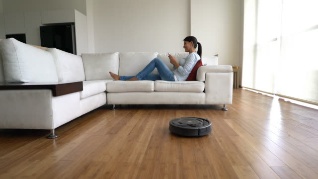 Woman chatting on phone while robotic vacuum does all the work