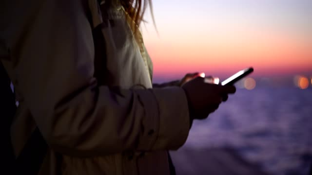 woman chatting online at sunset - cheerful stock videos & royalty-free footage