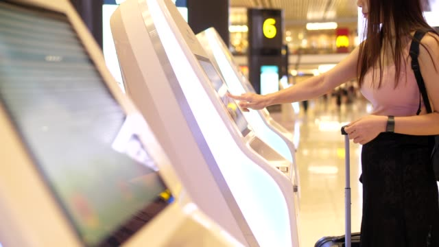 woman check in flight from kiosk machine - touch sensitive stock videos & royalty-free footage